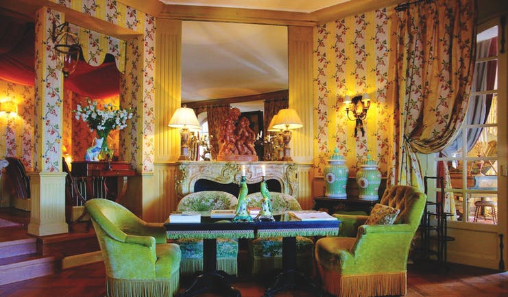 Villa Gallici Provence lounge with yellow and white floral striped wallpaper fireplace and a table and chairs