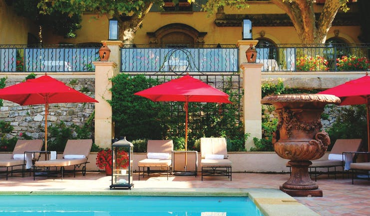 Villa Gallici Provence outdoor pool with sun loungers and red umbrellas
