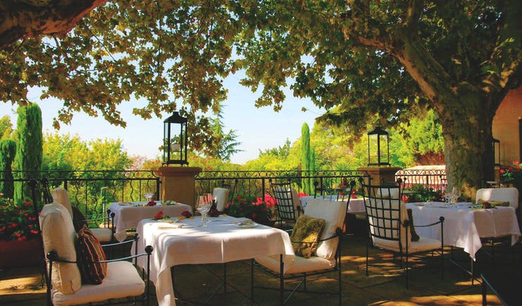 Villa Gallici Provence outdoor restaurant with several white tables and a tree
