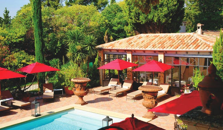 Villa Gallici Provence outdoor swimming pool with red umbrellas and two large urns