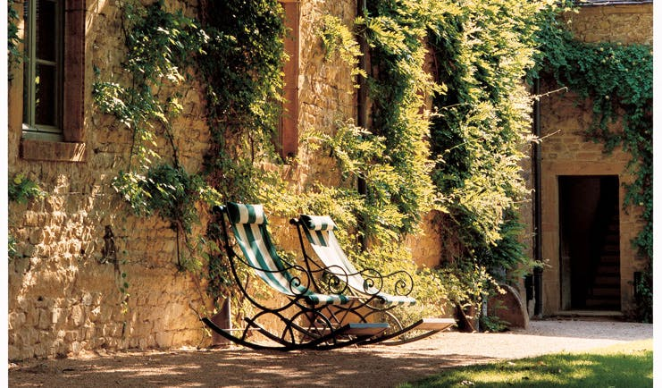 Chateau de Bagnols Rhone Valley outdoor seating two deck chairs outside wall with ivy