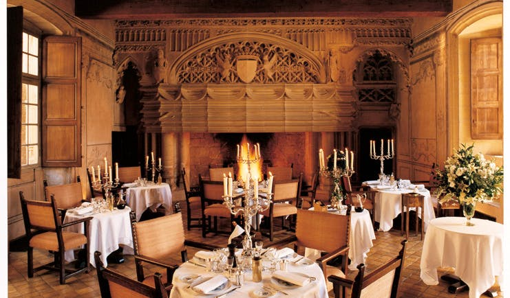 Chateau de Bagnols Rhone Valley restaurant indoor dining area with fireplace and candelabras
