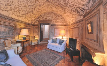 Chateau de Bagnols Rhone Valley suite lounge area with painted ceiling sofas armchair desk and fireplace