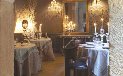 Hotel Cour des Loges Lyon dining area with three round tables with candelabras and a large mirror