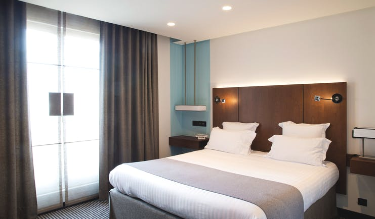 Room at the Hotel la Pyramide with double bed, bed side tables and large windows