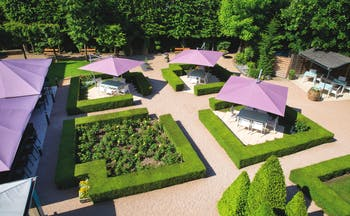 Aerial view of the gardens, showing freshly trimmed bushes and purple umbrellas
