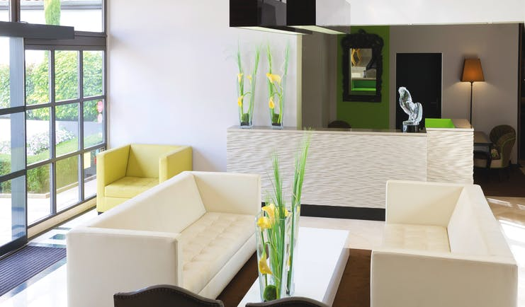 Lounge at the Hotel la Pyramide with cream coloured sofas and a green armchair