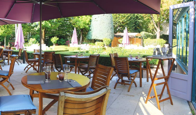 Outdoor terrace seating area with wooden tables and chairs set up around the patio with large purple umbrellas set up