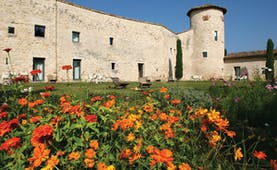 Exterior of hotel, showing a large stone building with lawn in front and orange flowers