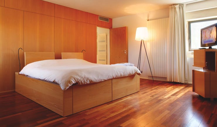 Chateau de Salettes Tarn and Lot grand confort bedroom with light wood walls and floor