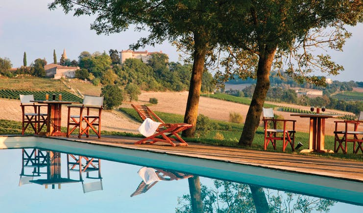 Chateau de Salettes Tarn and Lot outdoor pool overlooking fields with wooden sun loungers