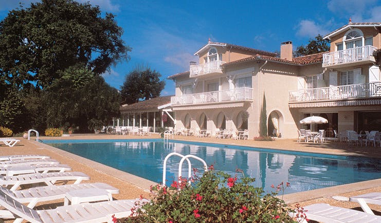 La Reserve Albi outdoor pool building with balconies overlooking outdoor pool with loungers
