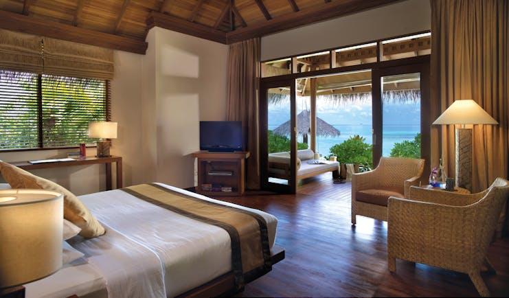 Baros Spa Maldives deluxe villa bed terrace elegant interior overlooking sea