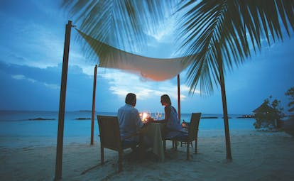 Coco Bodu Hithi beach dining, romantic couple dining on the beach in the evening