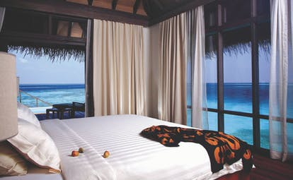 Coco Bodu Hithi escape water villa interior, bed, curtains, open walls leading to terrace, views out over the sea