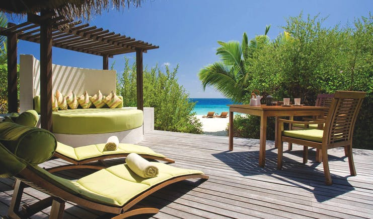 Coco Bodu Hithi island villa terrace, outdoor sofa, loungers, terrace leads directly on to beach