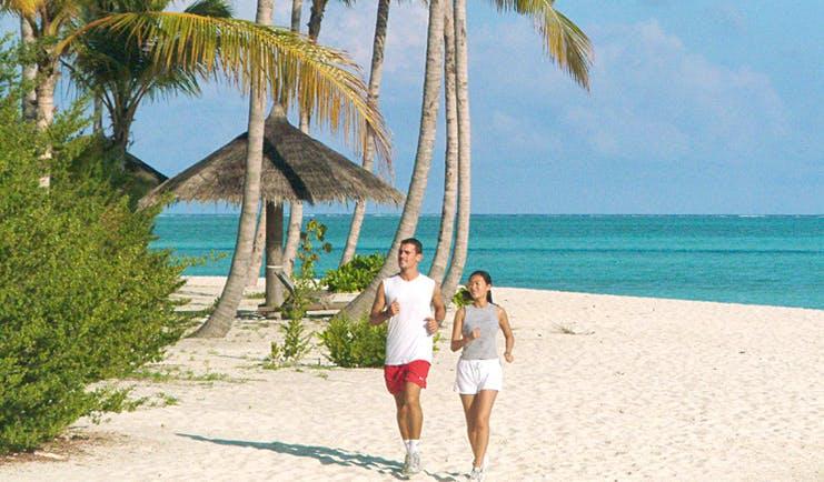 Conrad Maldives beach white sand clear blue water couple jogging