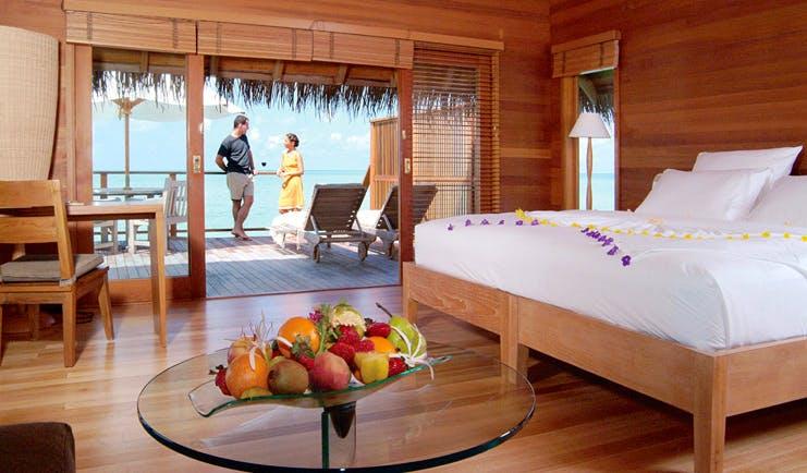 Conrad Maldives water villa interior bed terrace overlooking sea