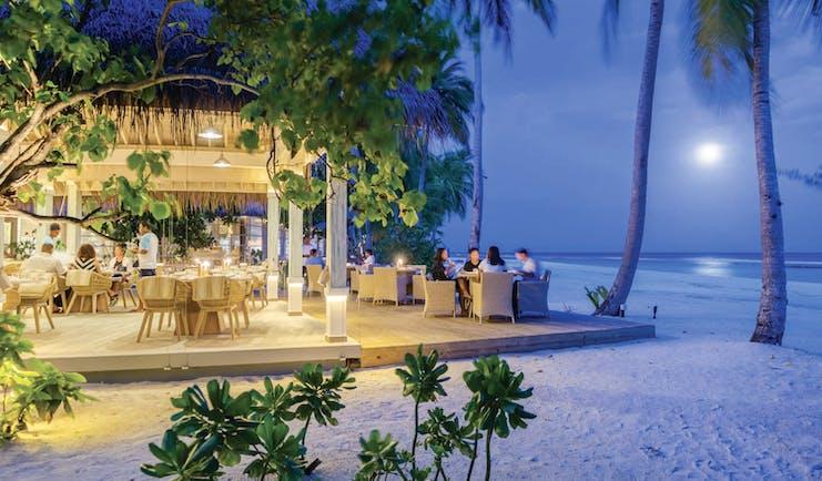 Finolhu beachside restaurant at night, diners eating, palm trees