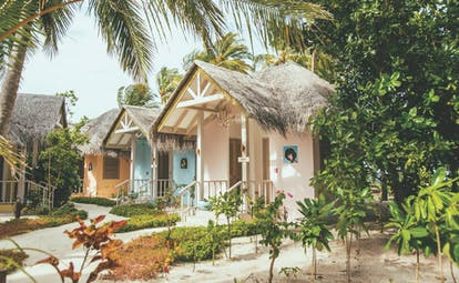 Finolhu cove club exterior, little buildings surrounded by lush greenery