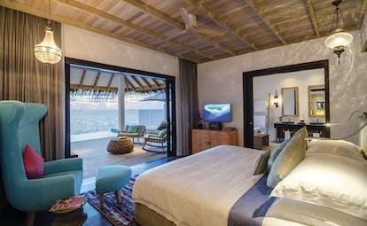 Finolhu ocean villa interior, bed, bathroom, doors to private terrace with pool, fresh modern decor