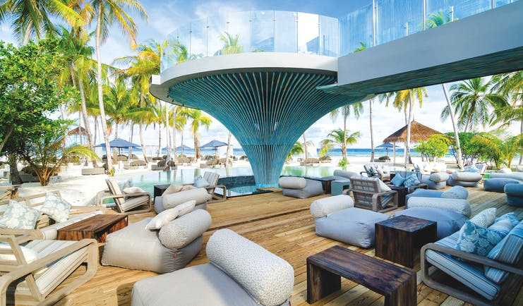 Finolhu pool terrace, bar seating area overlooking the pool, comfy chairs