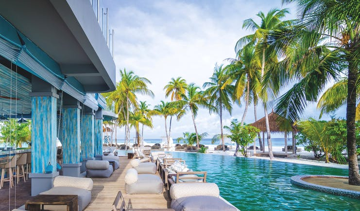 Finolhu poolside bar, terrace overlooking pool, outdoor armchairs