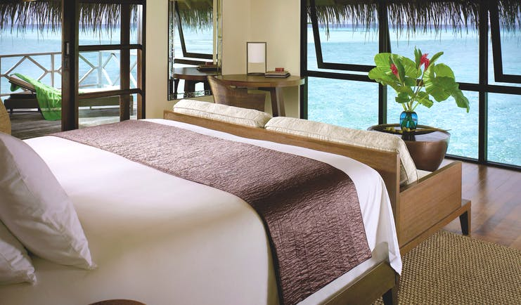 Four Seasons Kuda Huraa water bungalow interior double bed, modern interior, views of sea