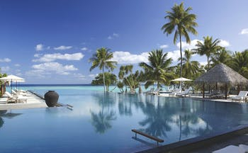Four Seasons Landaa Giraavaru Maldives infinity pool beach sun loungers palm trees
