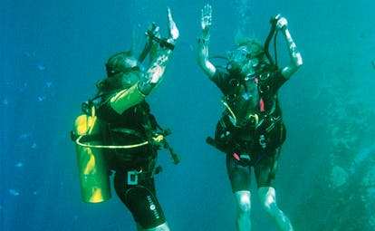 Two divers diving underwater in the ocean with oxygen tanks
