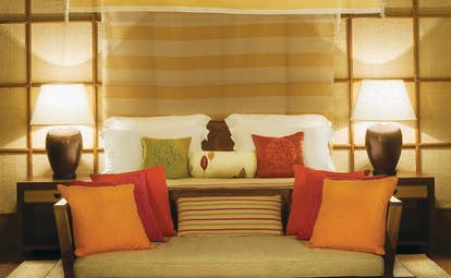 Water villa bedroom with double bed, sofa and lampshades on bedside tables