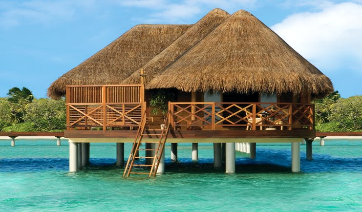 Water villa exterior with a beach hut style house shown above clear waters with steps leading down into the sea