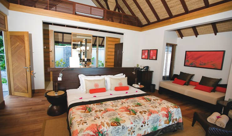 Lux Maldives diva suite bedroom, double bed, sofa and armchair, modern decor
