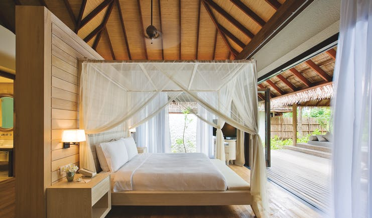Maalifushi garden suite bedroom, canopied bed, open terrace access, fresh modern decor