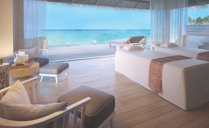 Maalifushi spa room, treatment beds, armchairs, mesh wall coverings allowing views out over the ocean