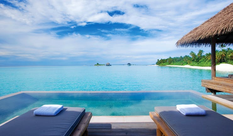 Maalifushi water villa infinity pool, overwater accommodation and terrace, views out to sea