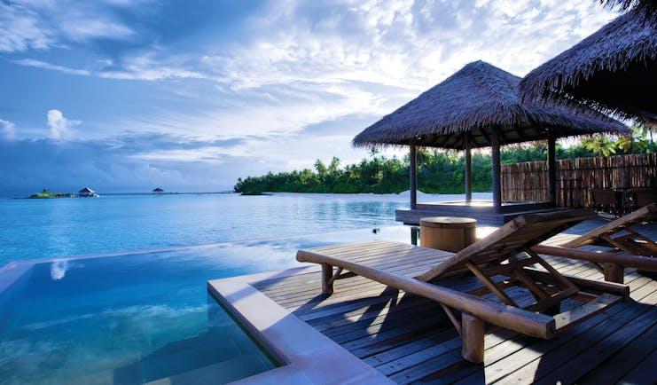 Maalifushi water villa terrace, infinity pool, sun loungers, views out to sea