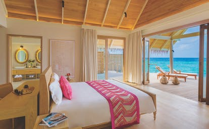 Milaidhoo water pool villa bedroom, double bed, doors leading to deck, modern decor, views over the sea