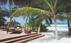 Naladhu Maldives restaurant deck on beach palm trees white sand ocean