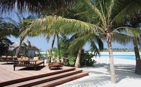Naladhu Maldives restaurant deck on beach palm trees white sand ocean