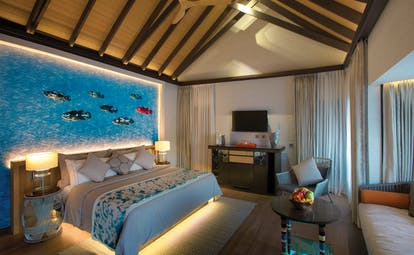 Wind villa with pool with large double bed, television and underwater art work on the walls