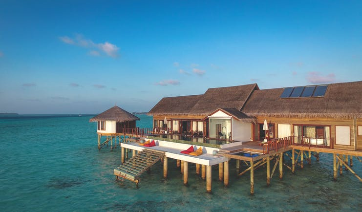 Water suite exterior with wooden building built on decking on top of the sea