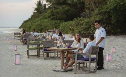 Soneva Fushi Maldives beach dining couples enjoying a drink on the beach helpful waiter