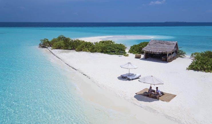 Soneva Fushi Maldives beach white sands clear blue ocean couple enjoying a picnic