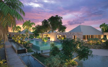 View of exterior of hotel and pool with pink sunset in the sky and hotel in back ground
