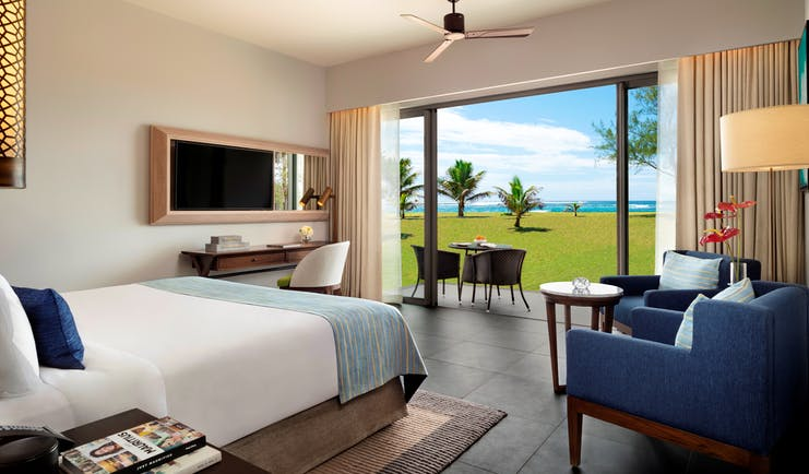 Hotel guest room with double bed, television, arm chair and doors opening onto terrace area