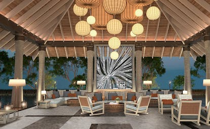 Lobby with lights hanging from ceiling seating areas around the room