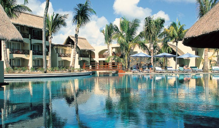 Constance Belle Mare Plage Mauritius poolside sun loungers umbrellas palm trees
