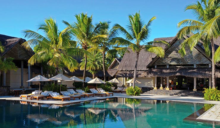Constance Le Prince Maurice Mauritius poolside sun loungers umbrellas palm trees