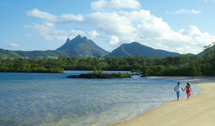 Four Seasons Mauritius beachfront couple walking on the beach wooded mountain